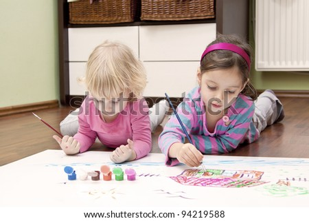 two sisters on the floor drawing a color house - stock photo