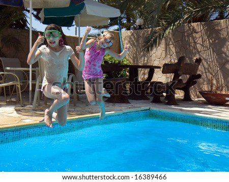 Two sisters on vacation playing in the swimming pool