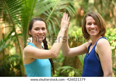 Two sisters or friends giving a high five - stock photo