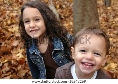 Two sisters playing in leaves in the fall - stock photo