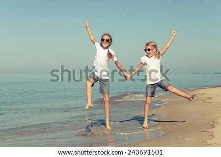 two sisters playing on the beach at the day time - stock photo
