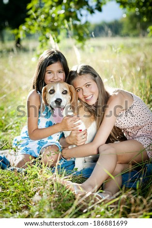 Two sisters playing with their beagle dog in green sunny park - stock photo