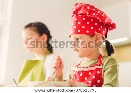 Two sisters preparing granola together. Happy siblings in the kitchen at home. Homemade granola / muesli - healthy eating concept - stock photo