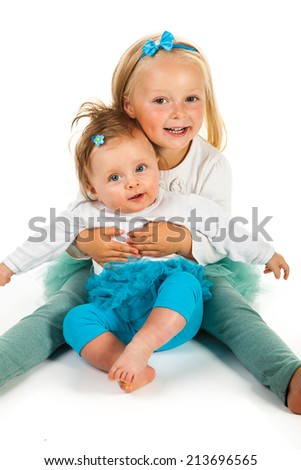 Two sisters preschool and newborn - stock photo