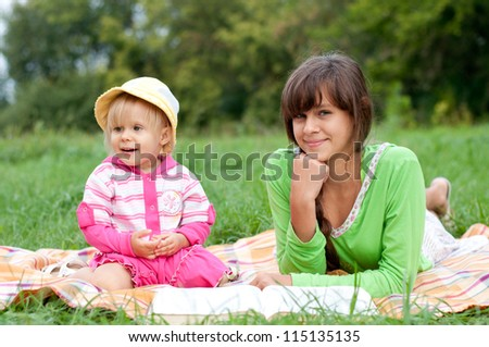 Two sisters reading a book outdoors