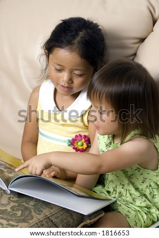 Two sisters reading a storybook together - stock photo