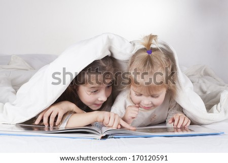 Two sisters reading bad time story in bad with white sheets - stock photo