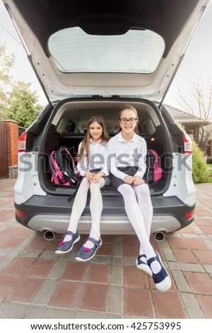 Two sisters ready to go to school sitting at open car trunk - stock photo