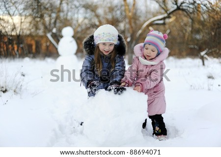 Two sisters rolling snow to make snowman
