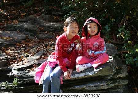two sisters sit together on rock - stock photo