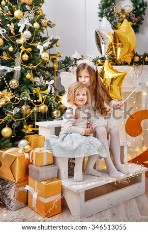 Two sisters sitting next to a Christmas tree and presents. New Year. Family celebration. Holiday and fun. Merry Christmas. 2017 - stock photo
