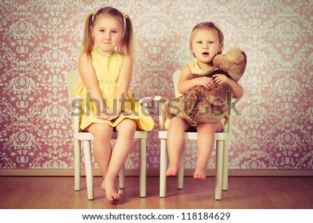 two sisters sitting on a retro chair - stock photo