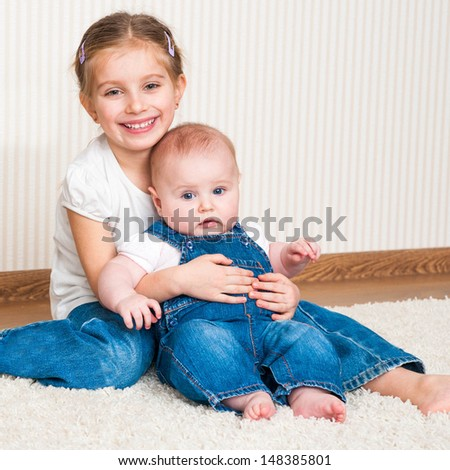 Two sisters sitting on the floor at home - stock photo