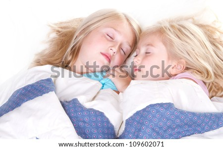 two sisters sleeping in bed - stock photo