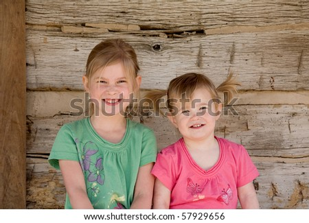 Two Sisters Smiling Big in Front of Home - stock photo
