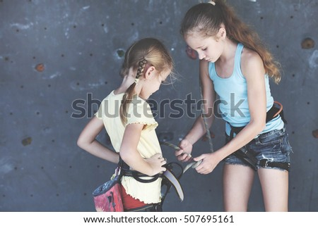 two sisters standing near a rock wall for climbing indoor