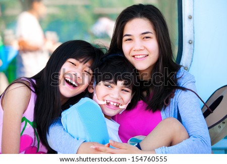 Two sisters taking care of disabled little brother. Child has cerebral palsy - stock photo