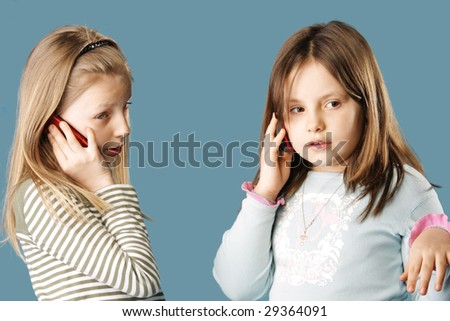 Two sisters talking by mobile phones simultaneously