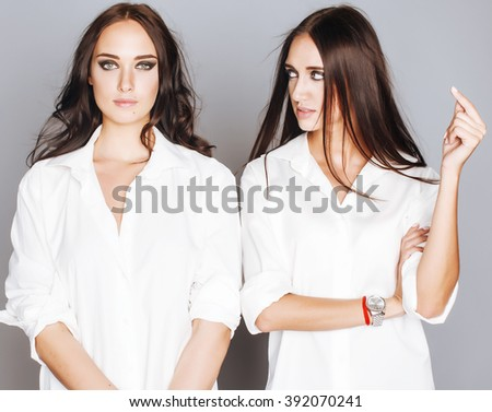 two sisters twins posing, making photo selfie, dressed same white shirt, diverse hairstyle friends - stock photo