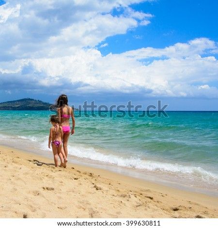 Two sisters walking on the beach in a summer day - stock photo