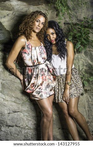 Two sisters with two personalities, strong and soft, long brown curly hair and long black curly hair, is confidently and charmingly standing by rocks and wild green leaves, looking at you./Two Sisters - stock photo