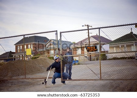 "Two skaters slip through a fence that reads ""No Trespassing"" - stock photo"