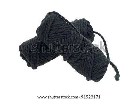 Two skeins of thick black yarn on a white background. - stock photo