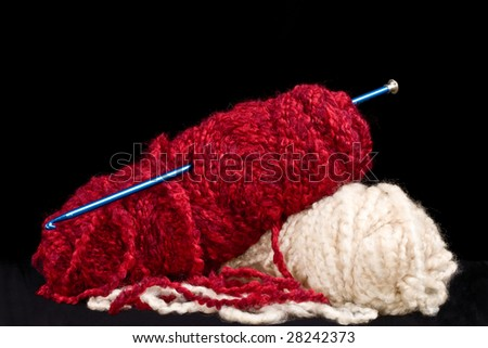 Two skeins of yarn, red and white with long crochet hook - stock photo