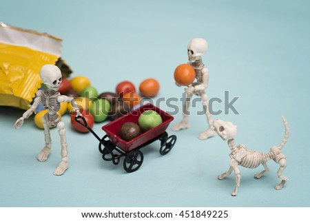 Two skeleton kids and skeleton dog getting chocolate candy - stock photo