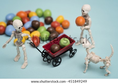 Two skeleton kids getting chocolate candy with red wagon - stock photo