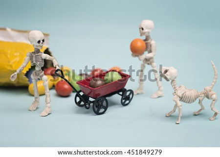 Two skeleton kids getting chocolate candy with toy wagon - stock photo
