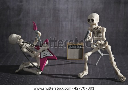 Two skeletons band playing rock music