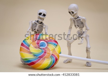 Two skeletons try to lift lollipop - stock photo