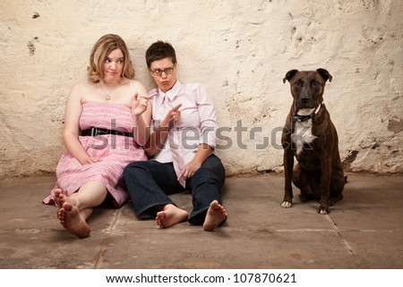 Two skeptical women pointing at a dog on leash - stock photo
