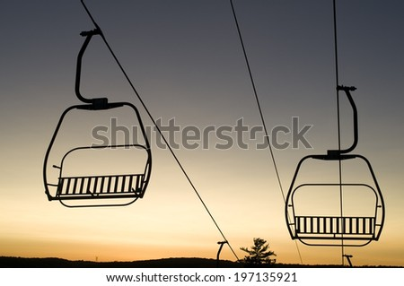 Two ski lift chairs sitting empty in twilight. - stock photo