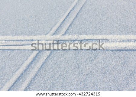 Two ski tracks which are crossed on snow in winter day - stock photo