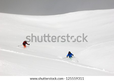 Two skiers descend an extreme slope in Utah, USA. - stock photo