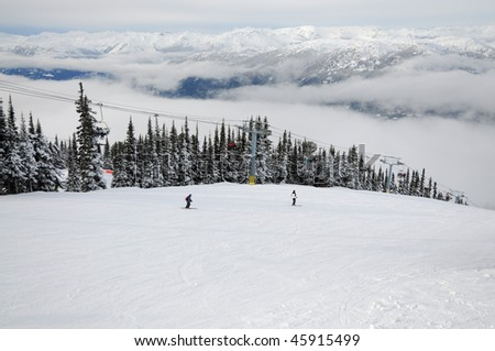 Two skiers sliding down the hill along a chairlift at Whistler-Blackcomb resort - stock photo