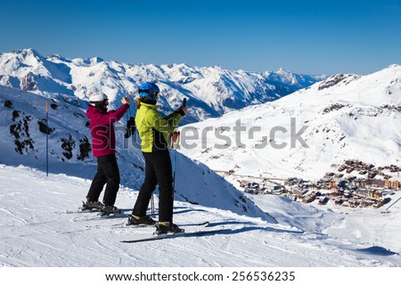 Two skiers taking photos over Val Thorens the highest ski resort in Europe - stock photo