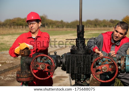 Two Skilled Oil and Gas Engineers in Action at Oil Well.Two oil and gas engineers working on oil rig equipment. - stock photo