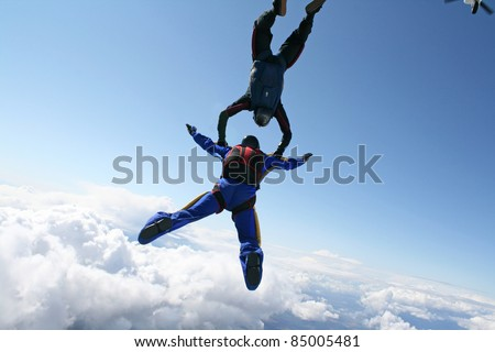 Two skydivers exit an airplane high up in the air - stock photo