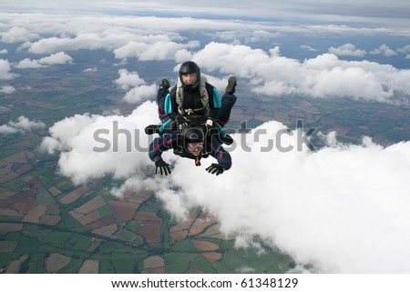 Two skydivers in freefall on a sunny day - stock photo