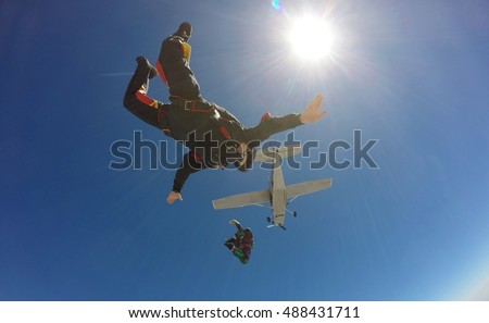 Two skydivers jump from an airplane