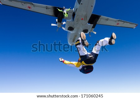 Two skydivers jump out of an airplane. - stock photo