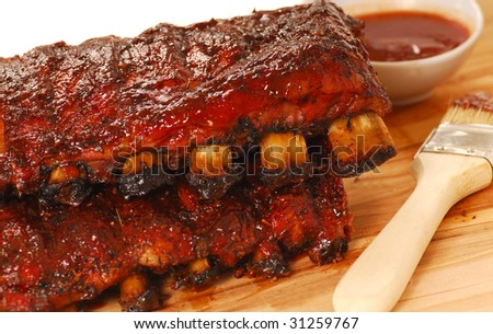 Two slabs of delicious BBQ spare ribs with dipping sauce - stock photo
