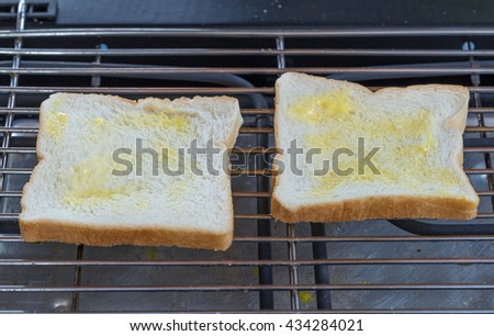 two slice of bread with butter on a toaster for breakfast. - stock photo