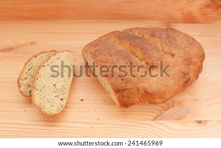 Two slices of bread cut from a fresh multi seed loaf on a wooden table - stock photo