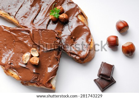 Two slices of bread with chocolate cream and hazelnuts white isolated top view. Hazelnut and chocolate decoration. - stock photo