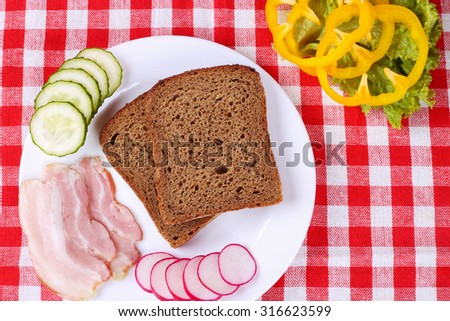 Two slices of brown bread, thinly sliced bacon, yellow peppers, cucumbers and radishes on the table.  - stock photo