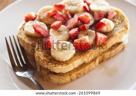 Two slices of French toast with sliced bananas and strawberries on top